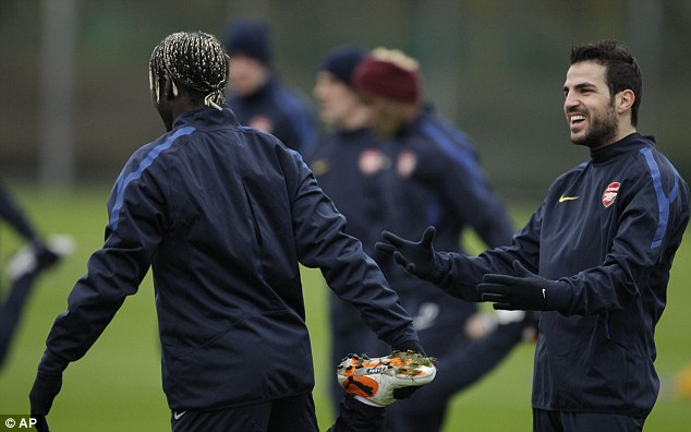 All smiles: Wenger says Arsenal are not holding Barcelona target Fabregas (right) against his wishes
