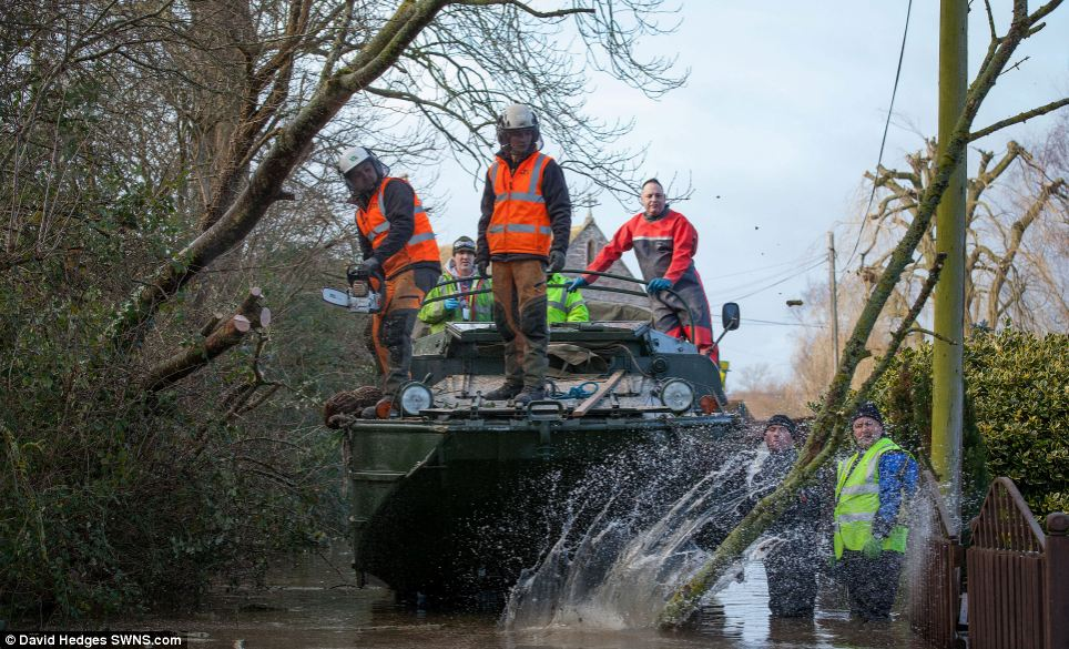 Volunteers on board a WW2, 1945 DUKW (colloquially known as Duck) which is a six-wheel-drive amphibious truck in Moorland, Somerset. Water levels remain extremely high, with the entire village underwater