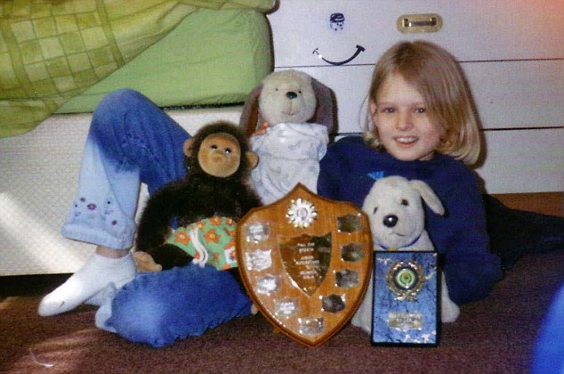 Posing with trophies - and some stuffed animals - Holly is pictured here aged 9
