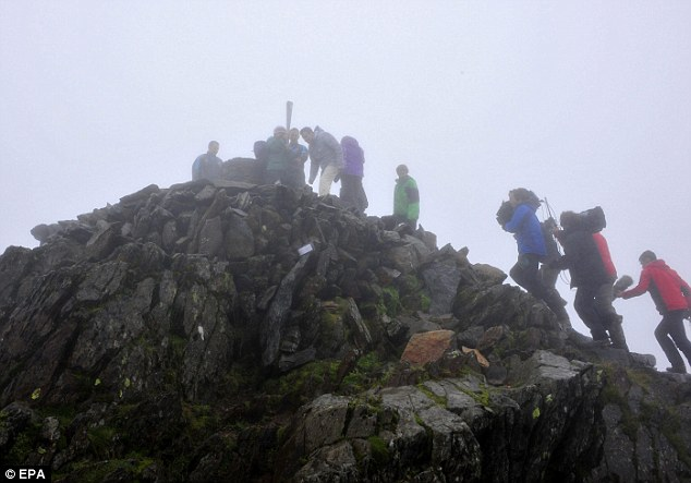 Ain't no mountain high enough: The Paralympic Flame held at the top of Snowdon, accompanied by Lord Coe
