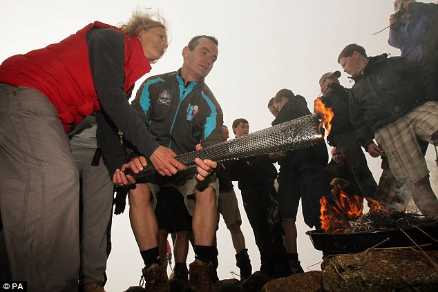 Ablaze: Blind mountaineer Bernadette Sloan lights a Paralympic Torchat the top of Slieve Donard