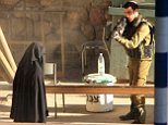 An Israeli soldier aims his rifle at a woman said to be 19-year-old Palestinian student Hadeel al-Hashlamun, before she was shot and killed by Israeli troops, at an Israeli checkpoint in the occupied West Bank city of Hebron September 22, 2015. The Israeli military said troops shot al-Hashlamun as she tried to stab a soldier. But relatives of al-Hashlamun denied the Israeli report saying she was executed. In a picture posted on Facebook, a soldier could be seen aiming his rifle at a woman said to be Hashlamun, standing a short distance away. She was completely covered in a black robe. REUTERS/Youth Against Settlements Group/Handout via Reuters?¢?Ǩ¬®?¢?Ǩ¬®ATTENTION EDITORS - THIS IMAGE HAS BEEN SUPPLIED BY A THIRD PARTY. IT IS DISTRIBUTED, EXACTLY AS RECEIVED BY REUTERS, AS A SERVICE TO CLIENTS. REUTERS IS UNABLE TO INDEPENDENTLY VERIFY THE AUTHENTICITY, CONTENT, LOCATION OR DATE OF THIS IMAGE. FOR EDITORIAL USE ONLY. NOT FOR SALE FOR MARKETING OR ADVERTISING CAMPAIGNS. NO SALES.