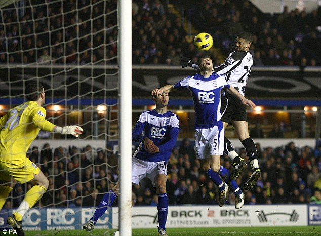 High riser: Leon Best (right) outjumps Roger Johnson to double Newcastle's advantage
