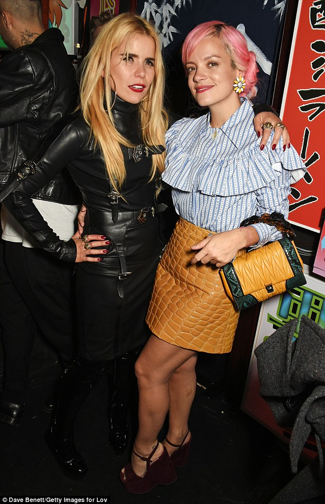 Music buddies: Lily Allen cosied up to singer Paloma Faith, who opted for a daring bondage style dress