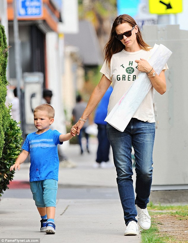 Tired: Jennifer looked care-worn as she collected son Samuel, three, from an art class later on Monday