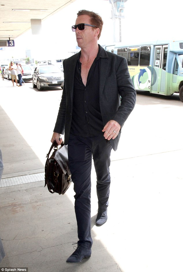 Mr swish! Homeland star Damien Lewis cut a suave figure as he arrived to catch his flight