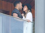 UK CLIENTS MUST CREDIT: AKM-GSI ONLY EXCLUSIVE: Rio de Janeiro, Brazil - John Legend and Chrissy Teigen display their Love while enjoying the view from their hotel balcony in Rio, Legend is currently in Town to perform during Rock in Rio music festival. Chrissy Teigen  took a few pictures and wore a maxi white cardigan over her blouse and Daisy Dukes showing off her long legs.  Pictured: John Legend and Chrissy Teigen Ref: SPL1134354  220915   EXCLUSIVE Picture by: AKM-GSI / Splash News