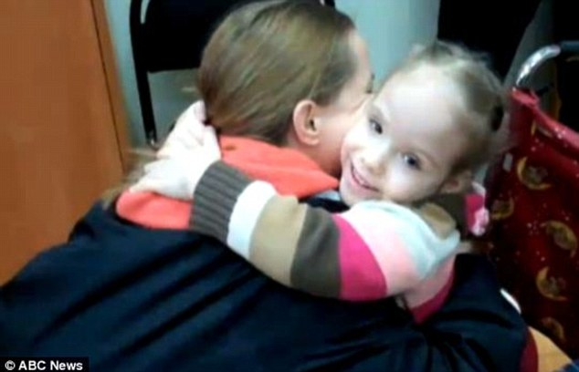 Blossoming: U.S. mother Kendra Skaggs hugs her adopted daughter, Polina, at an orphanage in Moscow last year after being given permission to adopt because her paperwork was filed just before the Russian ban