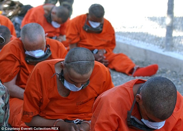 Controversy: Chained detainees are seen arriving at Camp X-Ray on Guantanamo Bay ahead of interrogation about their suspected involvement with terrorist groups including Al Qaeda or the Taliban