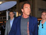 Arnold Schwarzenegger catching  flight at LAX wearinga blazer and a Terminator tee shirt