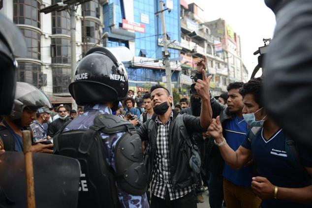 Nepalese police push back residents who began protesting after waiting for hours in line to board buses back to other towns and villages from Kathmandu on Ap...