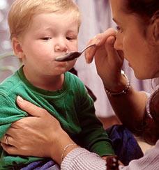 Child receiving medicine. Cough syrup