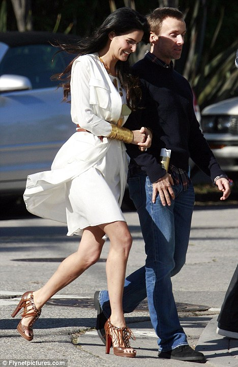 Smile for the cameras: Angie strolls arm in arm with a male friend on set