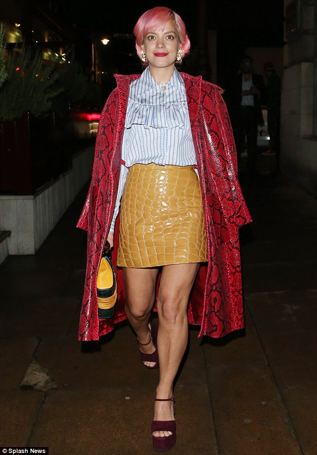 Edgy: Lily rounded off her colourful outfit with an eye-catching snakeskin print coat