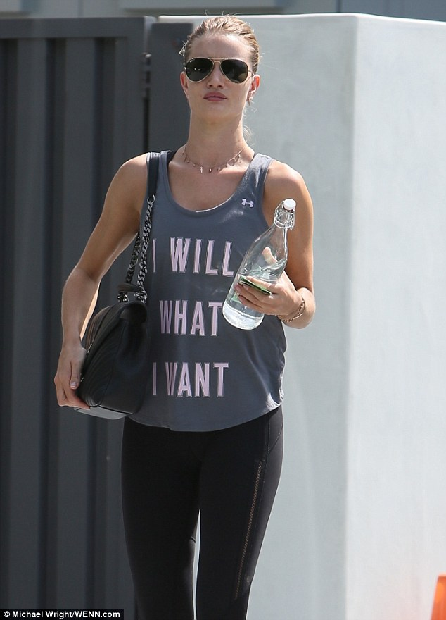 Standard issue: The rest of her look was gym-ready with the blonde wore a pair of tight three-quarter black leggings with an Under Armour tank with the phrase 'I Will What I Want' on it