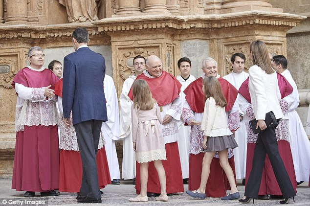Holy day: The family, led by King Felipe, meet the cathedral's priests ahead of the Easter service