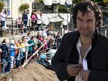 "PIC: PAUL WILLIAMS/APEX 23/09/2015 Filming on the second series of hit BBC drama Poldark has been held up by hordes of adoring sightseers trying to get a glimpse of hunk star Aidan Turner. The cast from the show has set up camp to shoot scenes for the latest series at the harbour in Charlestown, Cornwall. The village is a hub of activity with locals and tourists lining up to get a glimpse of the show's stars including Aidan Turner and Eleanor Tomlinson. But over eager fans have been causing problems. Simon Williams, manager of the Harbourside Inn in the village said it has been a busy few days. ""There's been a real buzz and it's definitely helped trade having the filming take place here,"" he said. ""Unfortunately a lot of people have been watching and taking pictures while filming and using flashes which I know has halted filming. ""When they shot here for the first season it wasn't busy as people didn't know who they were, but they do now as it's so popular."" This picture shows crowds"