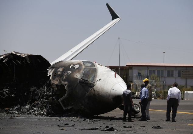 Officials of Felix Airways, a domestic airline, inspect a plane destroyed by Saudi-led airstrikes, at the Sanaa International airport, in Yemen, Wednesday, A...