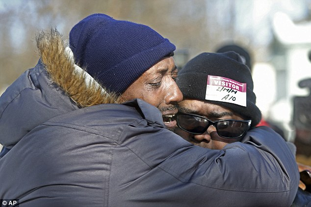 Regis Woodson and Chris Anderson embrace each other as they visit the home where a fire broke out Friday, Feb. 14, 2014, in Minneapolis