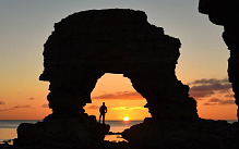 The autumn sun rises above the North Sea this morning framed through a natural sea arch on the rocky North East coast near South Shields