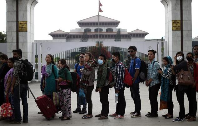 Nepalese residents wait to board buses at a main bus stand in Kathmandu on April 29, 2015