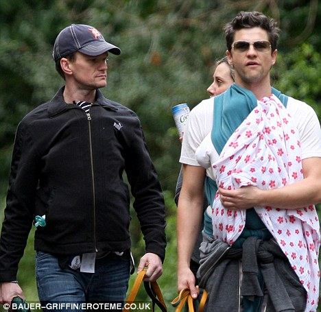 Daddy duty: The protective pair kept their twins covered during the outing