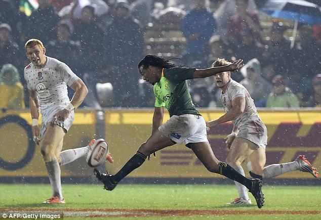 South Africa's Cecil Afrika (centre) kicks on the run as rain stream down during the Tokyo Sevens final