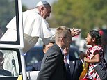 Pope Francis reaches for a child during a papal parade in Washington September 23, 2015. Pope Francis is making his first visit to the United States. REUTERS/Alex Brandon/Pool  Sophie Cruz