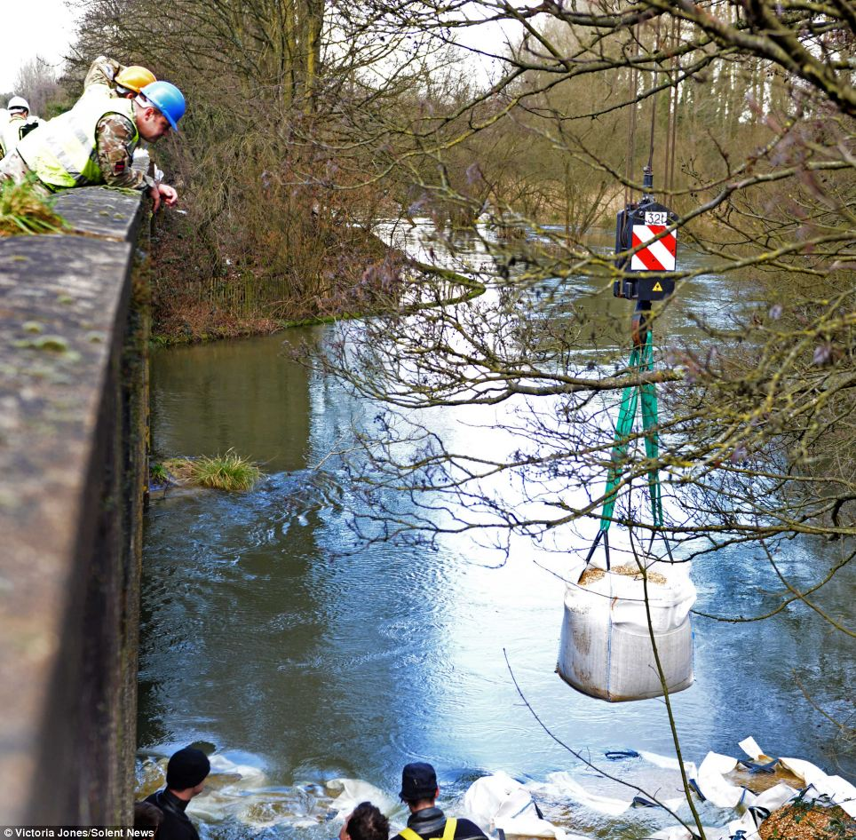 The Army load one tonne bags of aggregate into the river Itchen upstream from Winchester in an attempt to partially dam the river