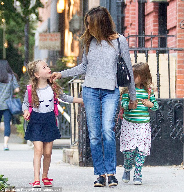 On the go: The 50-year-old, who lovingly caressed her daughter's face, is well known for her love of beautiful footwear on and off screen but a busy working mother can't be in high heels all the time