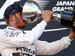 SUZUKA, JAPAN - SEPTEMBER 27:  Lewis Hamilton of Great Britain and Mercedes GP celebrates on the podium with the trophy after winning the Formula One Grand Prix of Japan at Suzuka Circuit on September 27, 2015 in Suzuka, Japan.  (Photo by Clive Rose/Getty Images)