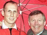 Manchester United manager Alex Ferguson embraces Dutch star Jaap Stam as he poses in a Manchester United shirt in pouring rain at Manchester's Old Trafford stadium, Tuesday May 5, 1998, after signing a deal making him the world's most expensive defender. Expected to be at the centre of the Netherlands' defence in the World Cup, Stam, 25, left PSV Eindhoven to sign a 10.75 million Pound (US$17.9 million) seven-year contract with United.(AP Photo/Dave Kendall)  **UNITED KINGDOM OUT**...S...SOC
