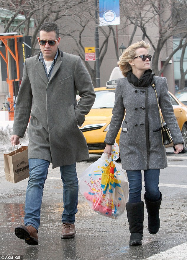 Man of style: The talent agent wore a chic grey trench coat, much like his wife's preppy button-up