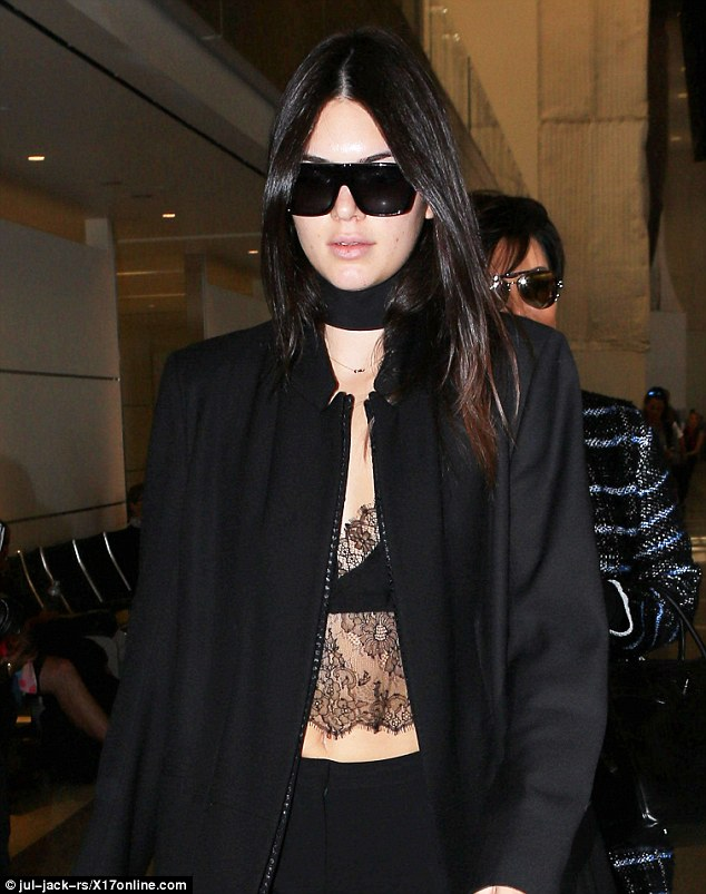 Sleek: The Keeping Up with the Kardashians star wore her long, raven tresses styled straight for the trip