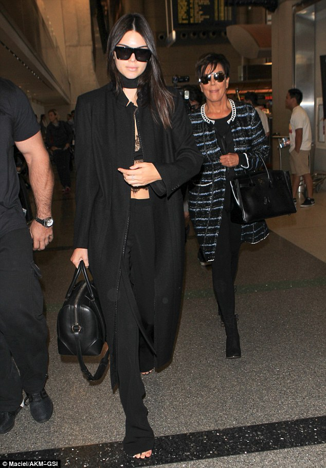 Keeping close: Kris followed closely behind her daughter Kendall as the pair made their way through the airport