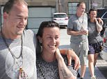 EXCLUSIVE TO INF.\nSeptember 27, 2015: Alanis Morissette in a pair of star patterned shorts and a cell phone case purse with a Ty Beanie baby attached to it shows off her tiger tattoo as she and husband Souleye, Magnus Palsson, in an indigenous-inspired necklace and drawstring shorts, bashfully smile as they stop for organic juice at Vintage Foods  in Malibu, CA. \nMandatory Credit: INFphoto.com Ref.: infusla-257/277/301