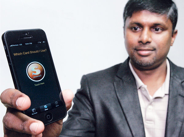 Senthill Palaniappan displays the Smorecard app for the iPhone which helps consumers determine which credit card to use at a store to get the best rewards back.  Glenn Moore/Tracy Press