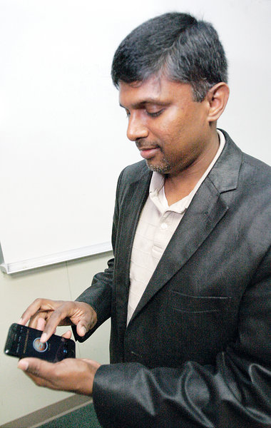 Senthill Palaniappan runs the Smorecard app to determine which credit card to use at a store to get the best rewards back.  Glenn Moore/Tracy Press