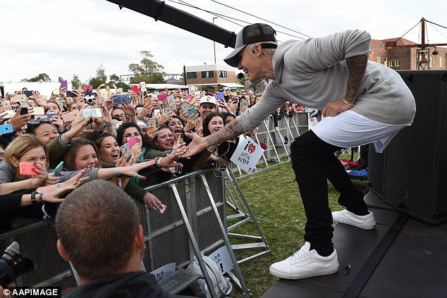 Greeting the fans: Bieber had girls screaming as he bent over and touched them on the hand mid performance