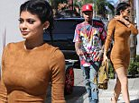 Kylie Jenner in skin tight suede dress, blue colored contacts,  with braided hair and major heels looking more and more like Kim every day. She's carrying aroun a broken iPhone and meet swith boyfriend Tyga after her meeting at Smashbox studios September 29, 2015 X17online.com