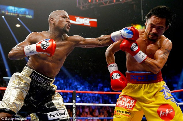 Mayweather (left) throws a punch at Pacquiao during their welterweight unification bout on Saturday