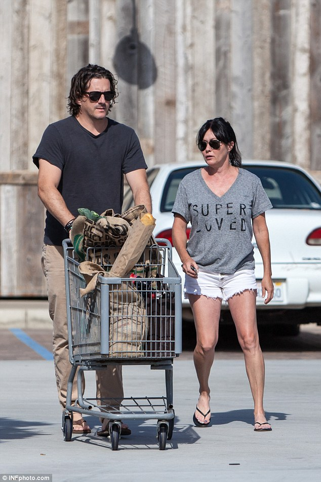 Fighting cancer: Shannen Dohertywore a T-shirt emblazoned with the words 'Super loved' as she shopped for groceries alongside husband Kurt Iswarienko in Malibu, California on Sunday