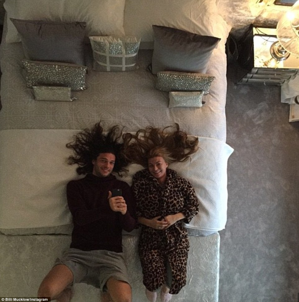 Mirror image: The pair pose for a social media photograph on their bed, showing off the fact they have a mirror on the ceiling