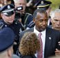 Republican presidential candidate and retired neurosurgeon Ben Carson is escorted as he walks through a crowd of students during a campaign stop at the University of New Hampshire Wednesday, Sept. 30, 2015, in Durham, N.H. (AP Photo/Jim Cole)