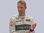 British McLaren F1 driver Jenson Button poses in front of his new branded car during a presentation, in Woking, England, Wednesday, Sept. 30, 2015. McLaren announced a new sponsorship deal with champagne brand Chandon.  (AP Photo/Frank Augstein)