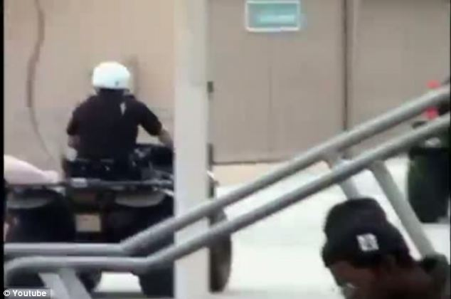 Not even the police can escape: An officer on a quad-bike is seen driving away from the scene