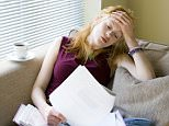 A young woman feeling stressed out with paperwork AAYTP7  young woman female girl caucasian white aged 16 17 18 19 20 21 22 23 24 25 26 27 28 29s 20's long red ginger light brown straight lifestyle life style lives people life-style british english uk united kingdom couch chair settee reclining recline sit living room lounge house home comfort contemporary modern light frustrate frustration stressed stressful stressing distress distressing worry worrying worried concern concerned tiring tired pressure shock shocking news bad homework college school work overtime paperwork form legal law issues themes threat threatening frighten frightening puzzled puzzling puzzle fill in complete document forms demand demanding payment bill invoice electric council bank statement card spending owe owed