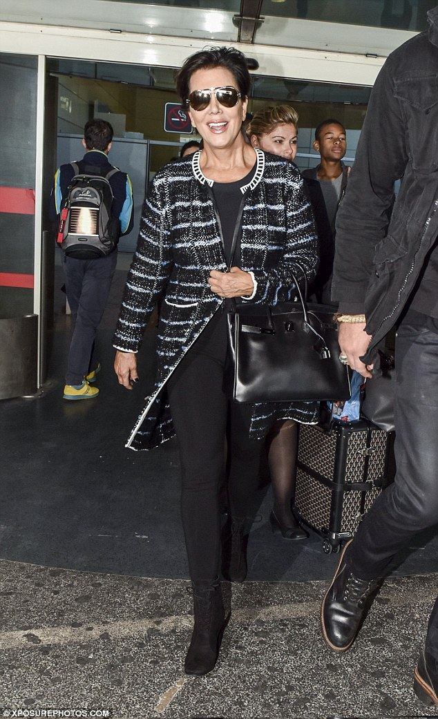 Touching down: Kris gave a wide smile as she arrived at the Charles De Gaulle airport that morning