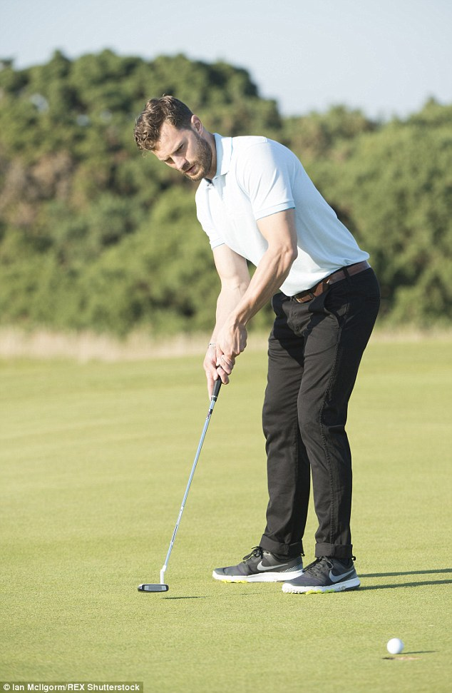 Look of concentration: The Northern Irish star was in a world of his own as he took a shot on the green
