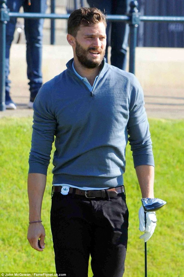 Looks the part: Jamie teamed black trousers with a blue shirt and jumper for his practice round